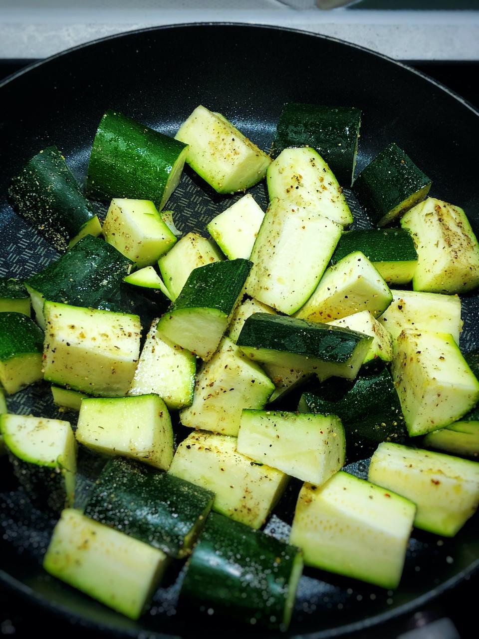 frying the zucchini in a pan