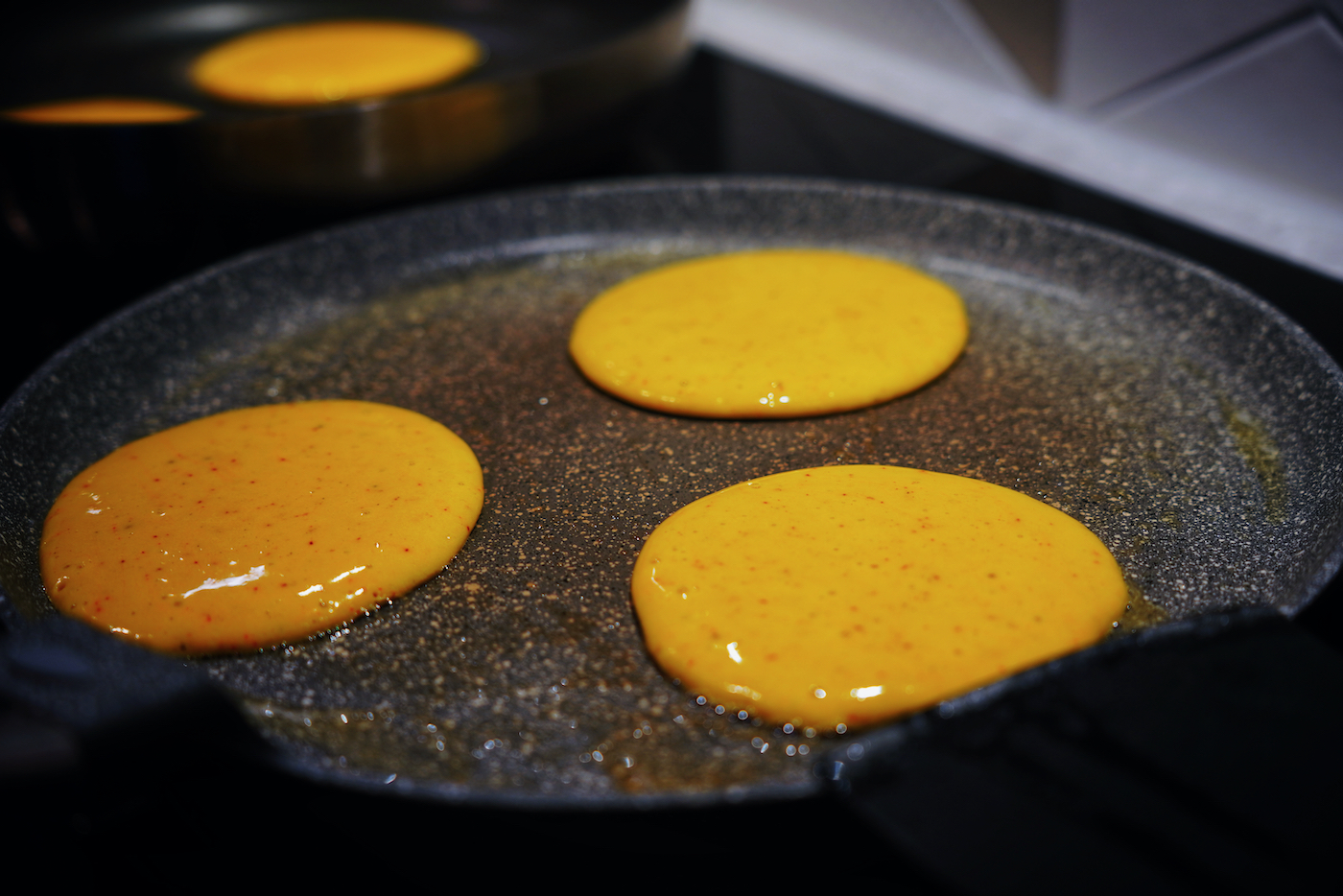 Banana and saffron pancakes in the pan