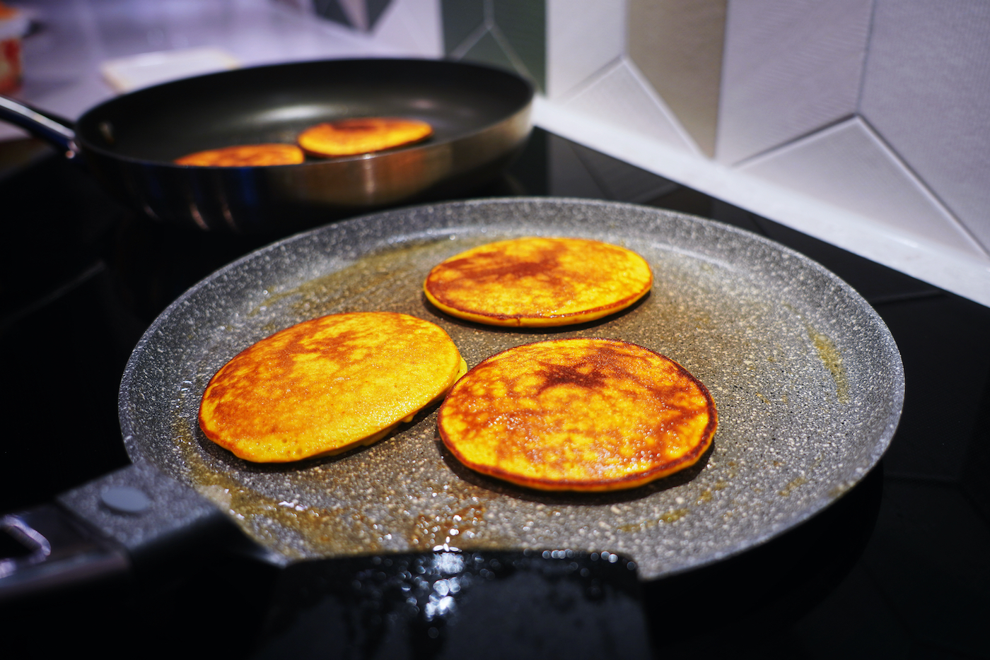 Banana and saffron pancakes in the pan fried on one side
