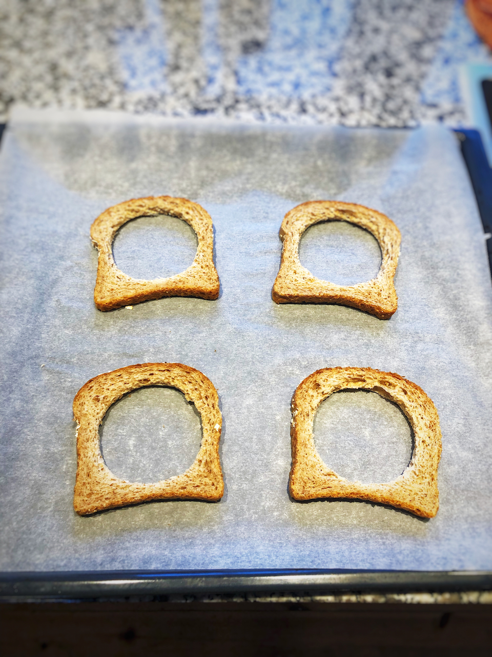 Take the 2 pieces of bread and make a round hole in the middle with a glass